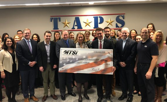Group of people together with senior leadership holding a check for Assistance Program (TAPS)