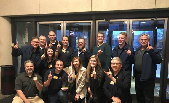 Photo of MTSI Dayton employees holding up their index fingers in a lobby