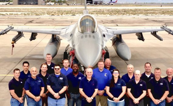 MTSI employees wearing MTSI polo shirts in front of fighter jet aircraft